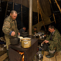 """North of the Arctic Circle in Russia, men from the last nomadic clan of Komi reindeer herders eat and drink in their chum (tepee), waiting for the calving season to begin. Left to right:  Alexei Semyashkin , Alexei Vauchesky, Arthum Khantazeski, and Fyodor """"Fedya"""" Vanutá (who is actually Nenet, not Komi, and unrelated to anyone else)."""