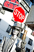 A man painted silver holds up a peace sign while standing on a street in New Orleans, Louisiana.