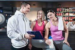 Young man showing clipboard to friends in gym
