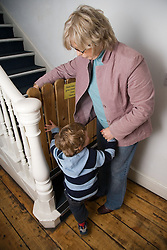 Young boy about to climb stairs at nursery; with his grandmother,