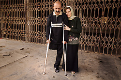 Salah Izat, 51, and his wife Amira Khalid, 44,  are seen outside their home in Baghdad, Iraq, March 2, 2004. Izat's home was destroyed in March 2003 when an American missile hit just outside their front door. A year later, Izat is getting better pay wages, but has lost his right leg from diabetes. He says the lack of medical resources after the war made him unable to get proper attention for his ailing leg, possibly being the reason it became so gangrenous that it had to be amputated.