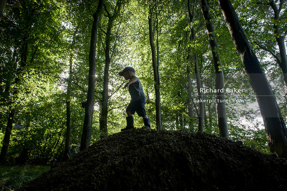 A four year-old boy plays below beech trees on a mound in Somerset woods. Running over the small hillock amid the trees, the woods look dark and menacing although sunlight is shining between the branches in the height of summer. The young lad enjoys the freedom of the great outdoors, experiencing the joys of boyhood - memories that last forever in a life lead outside in the wild.