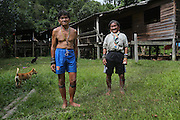 Twenty three years later: Penan natives, Baru standing with the brother of Banai Tebai. They lived twenty years ago in Long Tegan, but since the area was so thoroughly deforested, they moved upriver and now live in Long Gita. In a permanent traditional native design hardwood house on stilts. Limbang district, Sarawak, Borneo 2012<br /> <br /> Nomadic decades ago, now settled, far from their original hunter-gatherer grounds.<br /> <br /> The huge Petronas Sabah-Sarawak pipeline is being built across the Borneo rainforest through native areas. Petronas is the government cash cow which funds about 45% of its budget. New roads are being built, though much of the transport follows the existing roads and infrastructure created by logging. Whilst the government heralds the project as a source of jobs for local people, it is unlikely to bring much but wanton damage to rainforest habitat and paving the way for further deforestation by oil palm plantations. ..Borneo native peoples and their rainforest habitat revisited two decades later: 1989/1991-2012. ..Sarawak's primary rainforests have been systematically logged over decades, threatening the sustainable lifestyle of its indigenous peoples who relied on nomadic hunter-gathering and rotational slash & burn cultivation of small areas of forest to survive. Now only a few areas of pristine rainforest remain; for the Dayaks and Penan this spells disaster, a rapidly disappearing way of life, forced re-settlement, many becoming wage-slaves. Large and medium size tree trunks have been sawn down and dragged out by bulldozers, leaving destruction in their midst, and for the most part a primary rainforest ecosystem beyond repair. Nowadays palm oil plantations and hydro-electric dam projects cover hundreds of thousands of hectares of what was the world's oldest rainforest ecosystem which had some of the highest rates of flora and fauna endemism, species found there and nowhere else on Earth, and this deforestation has done ir