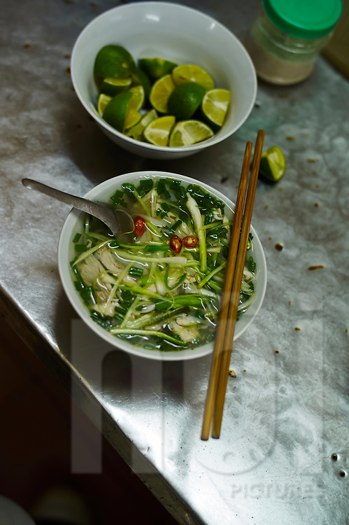 A bowl of chicken noodle soup, a dish also known as Pho Ga, sits on a table next to a bowl of sliced limes, Hanoi, Vietnam, Southeast Asia