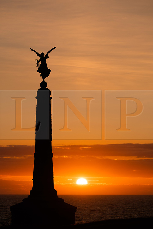 © Licensed to London News Pictures. 05/06/2019<br /> Aberystwyth,UK. The sun sets dramatically behind the distinctive silhouette of the winged angel of peace on top of Aberystwyth's seaside war memorial on the west Wales coast. The weather is set to become increasing ly wet over the coming days with some areas seeing significant rainfall amounts leading to potential flooding. Photo credit: Keith Morris/LNP