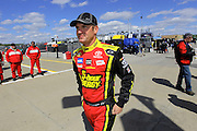 Clint Bowyer heads to the pit area before his qualifying run for a NASCAR Sprint Cup race at Kansas Speedway, Friday, April 19, 2013 in Kansas City, Kansas. (AP Photo/Colin E. Braley)
