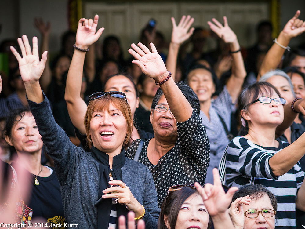 19 OCTOBER 2014 - BANG BUA THONG, NONTHABURI, THAILAND: Women cheer for ousted Prime Minister Yingluck Shinawatra at Apiwan Wiriyachai's cremation at Wat Bang Phai in Bang Bua Thong, a Bangkok suburb, Sunday. Apiwan was a prominent Red Shirt leader. He was member of the Pheu Thai Party of former Prime Minister Yingluck Shinawatra, and a member of the Thai parliament and served as Yingluck's Deputy Prime Minister. The military government that deposed the elected government in May, 2014, charged Apiwan with Lese Majeste for allegedly insulting the Thai Monarchy. Rather than face the charges, Apiwan fled Thailand to the Philippines. He died of a lung infection in the Philippines on Oct. 6. The military government gave his family permission to bring him back to Thailand for the funeral. His cremation was the largest Red Shirt gathering since the coup. The cremation Sunday had more political displays than previous funeral events but none of the politicians made any public statements.     PHOTO BY JACK KURTZ