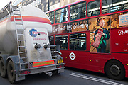 A bus and a cement truck show how large vehicles on the roads of London create a daunting prospect for other road users. UK.