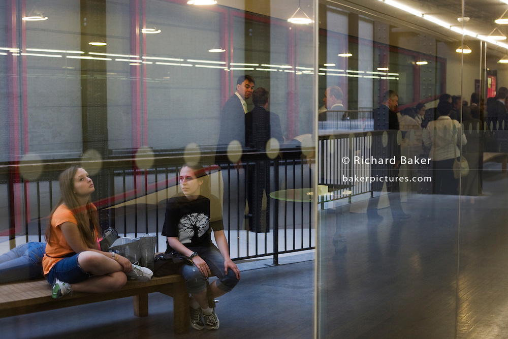 Two young women rest on a bench as executives talk behind glass.
