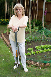 Woman resting on her spade by the vegetable plot,