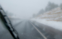 looking through an obstructed windshield with windshield wiper at unseasonable snowy weather along US 550 near the Continental Divide in NW New Mexico, USA  panorama