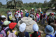 Israel, Northern District Ein Afek Nature Reserve on the Naaman River a group of children on a field trip stand by a set of mill stones