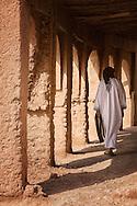 Traditional dressed man walks through an arch way inside a kasbah.