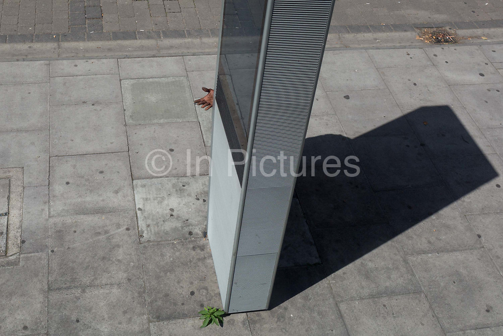 An anonymous man uses a free street phone service on the Walworth Road, on 25th July 2019, in London, England.