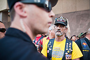 15 APRIL 2011 - PHOENIX, AZ: A member of the Tea Party confronts an Arizona Capitol Police officer who was protecting immigrants' rights activists at a Tea Party rally in Phoenix, Friday. About 500 supporters of the Tea Party movement rallied Friday at the Arizona State Capitol to mark tax day. They protested high taxes, the federal deficit, the debt limit and immigration policy. About 50 pro-immigrant protesters held a counter rally at the capitol. At least one person was arrested, and others led away by police after several shouting matches between Tea Party supporters and the immigrants rights protesters broke out.     Photo by Jack Kurtz