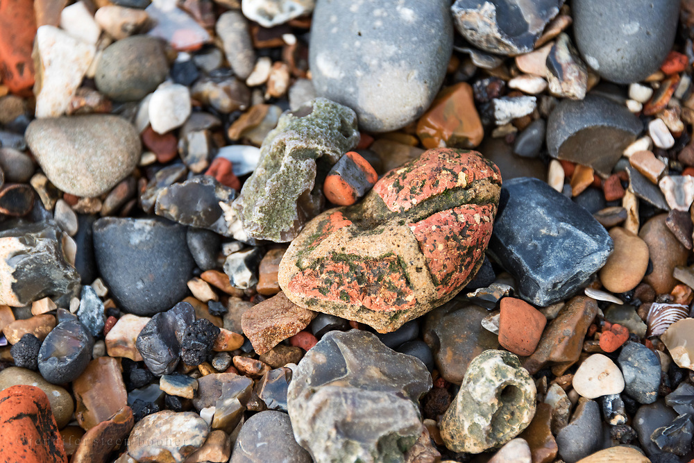 Brick rubble tumbled into a pebble shape, with fragments of flint and brick on the Thames shoreline, Greenwich, London.