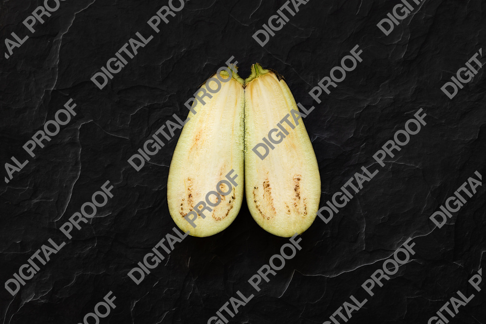 Isolated aubergine sliced at the middle isolated over a black stone background viewed from above - flatlay look