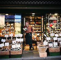 A wine merchant reads a book while waiting for customers to come to his store, which is located in the market on Rue Mouffetard in the Latin Quartier in Paris.<br /> <br /> NOTE: Larger resolution versions of these images are available on request.