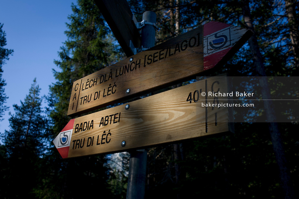 Hiking trails signpost near the rural lake 'Lêch della Lunch' in the Badia Dolomites, south Tyrol. Italy. The location is above the town of Pedraces/Badia Abtei and is seen early morning as the sun shines off the signpost, in  a summer pine forest.