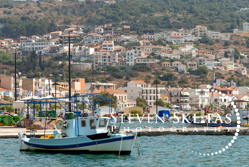 Samos. Greece. Colourful fishing boats in the harbour of Vathy or Samos town which is the Islands capital and largest town. The bustling waterfront of Vathy is adorned with neo-classical buildings many topped with red tiled roofs and the town rises steeply into wooded hills above.
