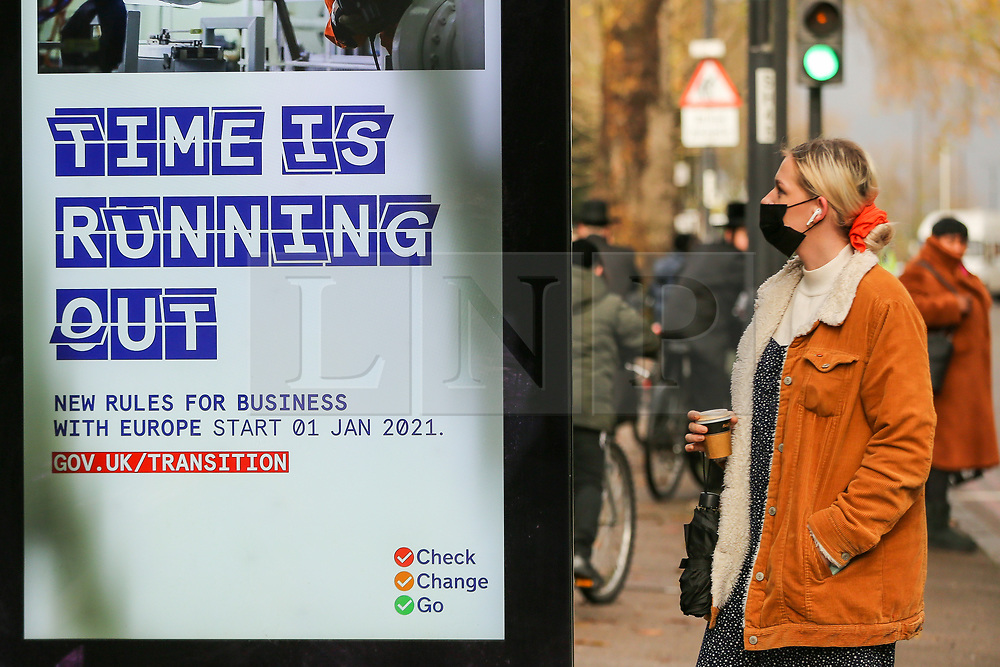 """© Licensed to London News Pictures. 11/12/2020. London, UK. A woman wearing a face covering views at the government's publicity campaign 'TIME IS RUNNING OUT', a poster for firms that trade with Europe to prepare for a no-deal Brexit. Prime Minister, BORIS JOHNSON has said that it is """"very, very likely"""" that the UK will agree to trade agreement with the European Union, and raising the prospect of a no-deal Brexit at the end of this month, when the UK leaves the EU. Photo credit: Dinendra Haria/LNP"""