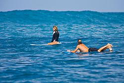 Surfer couples, enjoying riding rare big ocean waves in Kona Coast, Keauhou Bay, Big Island, Hawaii, Pacific Ocean