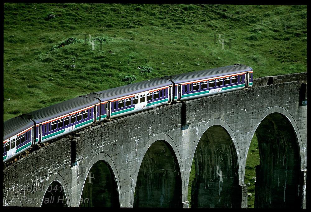 Scotrail passenger train crosses Glenfinnan Viaduct, 100'-tall, 21-arch concrete marvel (built 1901) seen in Harry Potter films; Scotland.