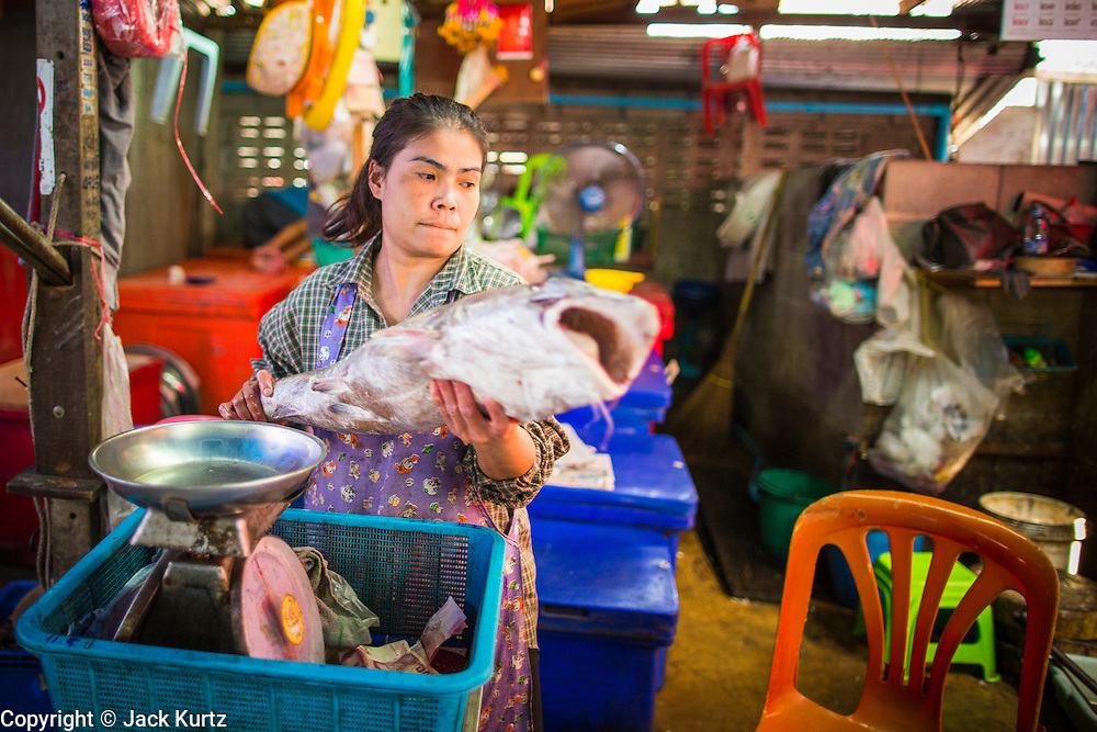 17 JANUARY 2013 - SAMUT SONGKHRAM, SAMUT SONGKHRAM, THAILAND:  A fish monger in the Samut Songkhram market weighs a fish before selling it. Four trains each day make the round trip from Baan Laem, near Samut Sakhon, to Samut Songkhram, the train chugs through market eight times a day (coming and going). Each time market vendors pick up their merchandise and clear the track for the train, only to set up again when the train passes. The market on the train tracks has become a tourist attraction in this part of Thailand and many tourists stop to see the train on their way to or from the floating market in Damnoen Saduak.    PHOTO BY JACK KURTZ