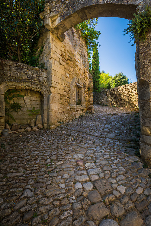 """Oppède is a commune in the Vaucluse department in the Provence-Alpes-Côte d'Azur region in southeastern France. Oppidum is the Latin word for 'town'. It is in fact two villages: Oppède-le-Vieux (""""the old"""" in French), built against the Petit Luberon and dating back to the 12th century, and Oppède-les-Poulivets (""""nice view"""" in Provençal), today known as """"le village"""", down in the valley.<br /> <br /> The old village, built on a rocky hill, has narrow streets. In winter, the Petit Luberon starts casting its shadow early in the afternoon. Houses beyond the medieval ramparts are dark, humid and tricky to maintain. From below the village is dominated by the restored church of Notre-Dame-Dalidon and the ruins of the castle. In the 19th century, the inhabitants had enough and started to move down in the valley, dismantling the roof of their houses to stop paying property taxes.<br /> <br /> By the beginning of the 20th century, Oppède-le-Vieux was a ghost village and a new community was officially established in the valley, with larger streets, cosier houses and farmers closer to their fields.<br /> <br /> Following the armistice of June 1940, architect Bernard Zehrfuss founded a commune of artists in the old town, a project that attracted French sculptor François Stahly and the writer and artist Consuelo de Saint Exupéry. The commune proved short-lived. It was the basis for Saint Exupéry's fictionalized account, published in 1946, called """"Kingdom of the Rocks"""".[2]"""