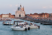 """Every year during Redentore Festival weekend, Venice builds a temporary pontoon bridge for pedestrians to walk 330 meters across Giudecca Canal from the Zattere to Redentore basilica on Giudecca Island, Italy. Venice built """"Il Redentore"""" (Church of the Most Holy Redeemer, or Chiesa del Santissimo Redentore) from 1577-1592 on Giudecca Island in Venice Lagoon, in thanksgiving for the end of a 1576 wave of plague. Redentore Festival (Redentore Festa, photo July 16, 2011) began as a feast of thanksgiving for the end of the terrible plague of 1576 which killed more than a quarter of Venice, some 46,000 in the city and 94,000 in the lagoons. (A worse round of Black Death swept Venice in 1629-30, after which Venice built the Salute, the last of its """"Plague churches."""") The religious celebration and popular feast of Redentore is held in Venice every the third Saturday and Sunday in July, with fireworks on Saturday night. Venice (Venezia), the """"city of canals,"""" is the capital of Italy's Veneto region, named for the ancient Veneti people from the 10th century BC. Venice and the Venetian Lagoons are on the prestigious UNESCO World Heritage List."""