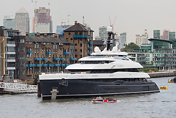 © Licensed to London News Pictures. 04/07/2018. London, UK.  A small union jack covered boat passes the new 243 feet long superyacht, Elandess, which arrives in London for the first time ever on the River Thames and moors at HMS President, the Royal Navy Reserve Unit next to St Katharine Docks and Tower Bridge this evening. Elandess was built at the Abeking and Rasmussen shipyard in Germany, launched in May 2018 and has just completed sea trials ahead of its London visit. Elandess has an axe-bow, dark hull and low-slung superstructure. There are a variety of entertaining communal spaces, from the 8 x 2.5-metre superyacht swimming pool located on the massive sun deck to the Nemo Lounge with portholes below the waterline and an observation lounge on the upper deck. Guest accommodation includes six staterooms, including the master suite which is placed forward on the main deck with an observation lounge directly above on the upper deck.  Photo credit: Vickie Flores/LNP