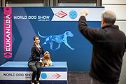 A dog owner is posing for a photograph with her dog at a photo opportunity point located on the Leipzig Trade Fair . Over 31,000 dogs from 73 nations will come together from 8-12 November 2017 in Leipzig for the biggest dog show in the world.