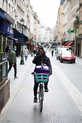 A cyclist crosses Montorgeuil street in Paris on May 4, 2020, on the forty-ninth day of a strict lockdown in France, in place to attempt to stop the spread of the new coronavirus (COVID-19). Photo by Raphael Lafargue/ABACAPRESS.COM