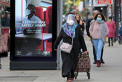© Licensed to London News Pictures. 11/10/2020. London, UK. A woman wearing a face shield walks past 'Keeping You Safely Apart' advert in Wood Green, north London as another national coronavirus lockdown looms. <br /> SADIQ KHAN, Mayor of London has warned that a London lockdown cannot be ruled out as coronavirus cases in the capital soar. In a statement to MPs on Monday, 12 Oct 2020, Prime Minister Boris Johnson is expected to announce tougher local restrictions, outlining plans for a three-tier system, where each region in England is placed into a tier based on the severity of cases in the area. Photo credit: Dinendra Haria/LNP