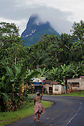A woman is walking on the road leading to Pico Maria Fernandes, on the island of Sao Tome, Sao Tome and Principe, (STP) a former Portuguese colony in the Gulf of Guinea, West Africa.