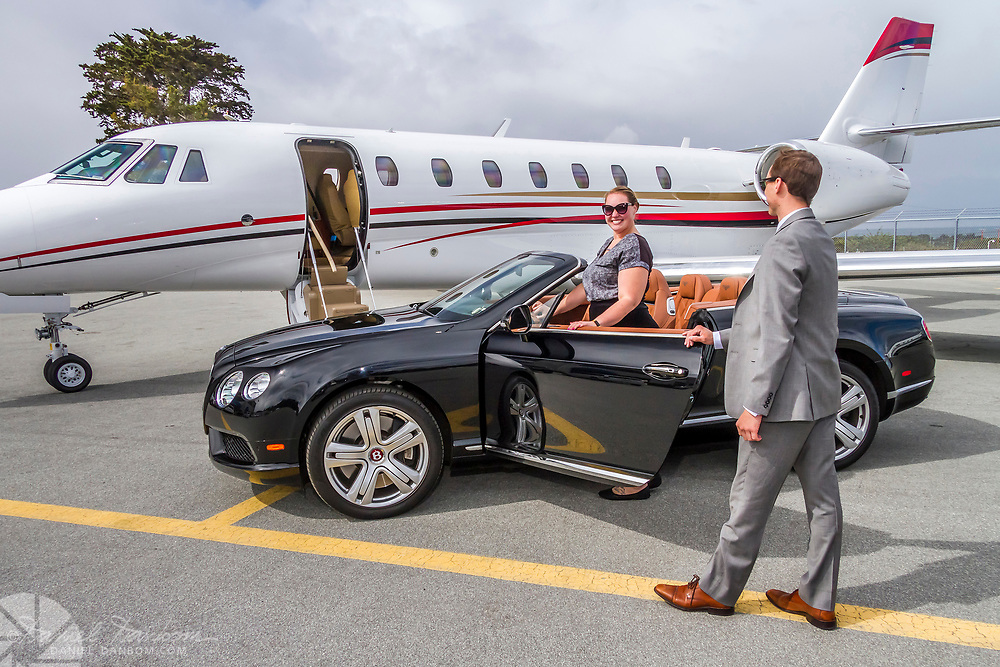 The luxury car rental agent helps client into luxury Bentley convertible at the ramp with a corporate jet.