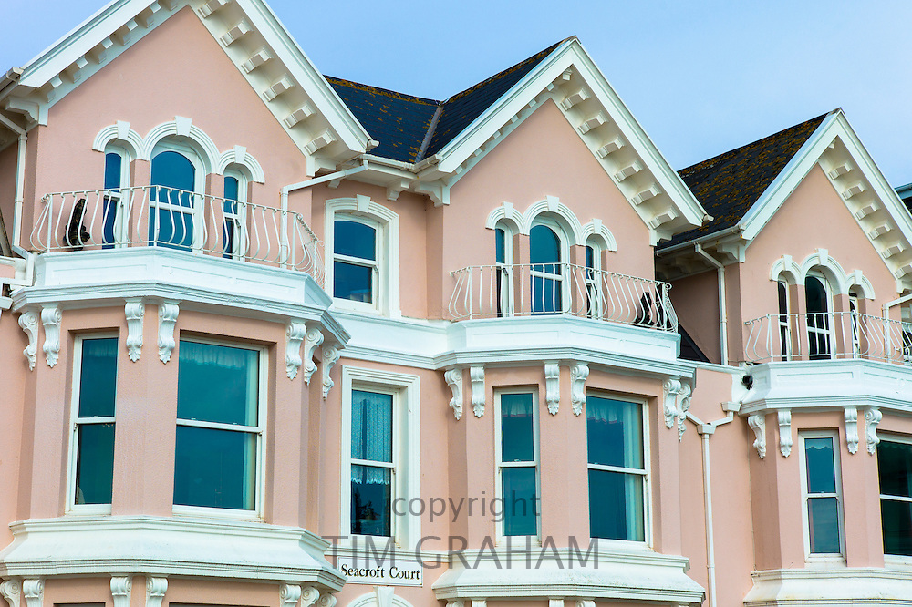 Pastel pink painted traditional seafront apartments at Seacroft Court along the English coast at Teignmouth in South Devon, UK