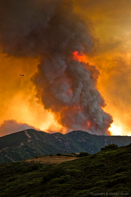 A smoke plume from a burning hillside rises quickly, changing the daylight to yellow and reddening the sun, at the La Brea Fire. Smoke from wildfires brings complaints from those living nearby, a strong political force that effects how wildland fire is fought and managed.