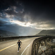 Female athlete running over a bridge in the mountains during a storm near Lake Tahoe, CA.
