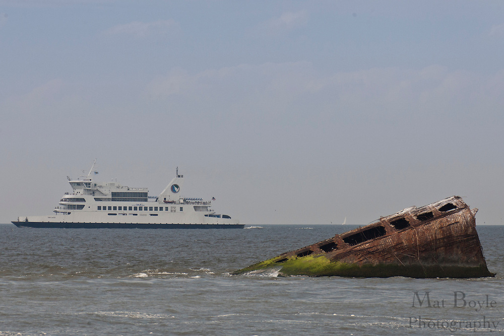 The Cape May-Lewis ferry passes by the concrete ship Atlantus just off the coast of Sunset Beach Cape May NJ. The Atlantus was the second prototype concrete ship built duirng World War 1 because of the shortage of steel.