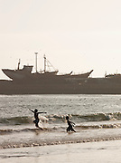 Young children play in the waves of the ocean while ships are moored and repaired at the dock across the bay in Essaouira, Morocco