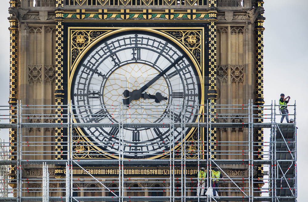 © Licensed to London News Pictures. 12/10/2017. London, UK. A scaffolder (R) takes a photo on from The Elizabeth Tower, known as Big Ben at Parliament. Scaffolding will reach a height of 96 meters when completed - the work is part of a three-year programme to conserve the Great Clock, the Elizabeth Tower and Big Ben. London, UK. Photo credit: Peter Macdiarmid/LNP