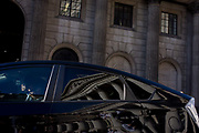 Pillars and architecture of the Bank of England and reflected architecture in dark windows and polished bodywork of an official's car, stopped in traffic. Two occupants of the car, stopped in traffic, sit looking forward while the reflections of the classical pillars and columns of Royal Exchange in Cornhill. The Exchange is opposite the Bank in Threadneedle Street in the heart of the capital's financial district - also known as the Square Mile - founded by the Romans in AD43. The Bank of England is Britain's monetary and fiscal controlling authority.