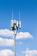 3 sector cellular telecom communications panel antenna array for the mobile telephone system on a cellsite pole tower against cumulus clouds. <br />
