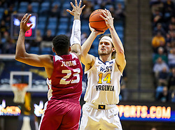 Nov 28, 2018; Morgantown, WV, USA; West Virginia Mountaineers guard Chase Harler (14) shoots over Rider Broncs guard Stevie Jordan (23) during the second half at WVU Coliseum. Mandatory Credit: Ben Queen-USA TODAY Sports