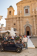 A classic Fiat awaits the bride and groom from a wedding held at Chiesa Madre Parrocchiale di San Tommaso di Canterbury, Marsala, Sicily.