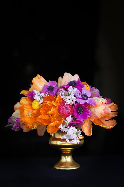 Bright flower arrangement in gold vase