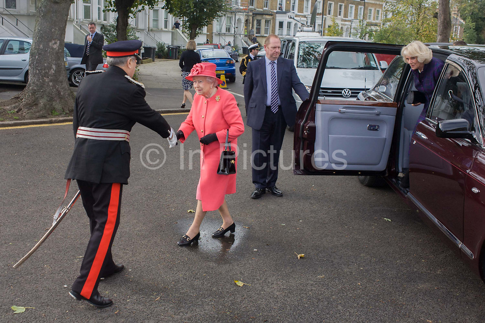 Queen Elizabeth exits her Bentley limousine to shake the hand of a Lord Lieutenant while making a brief visit to the Ebony Horse Club at Loughborough Junction, Brixton, London. Accompanied by the Duchess of Cornwall, Her Majesty watched an equestrian demonstration in one of the most disadvantaged inner city neighbourhoods in the country where there is a historic legacy of under-achievement in schools, high rates of teenage pregnancy and negative stereotypes of young people, gang violence and drug related crime.