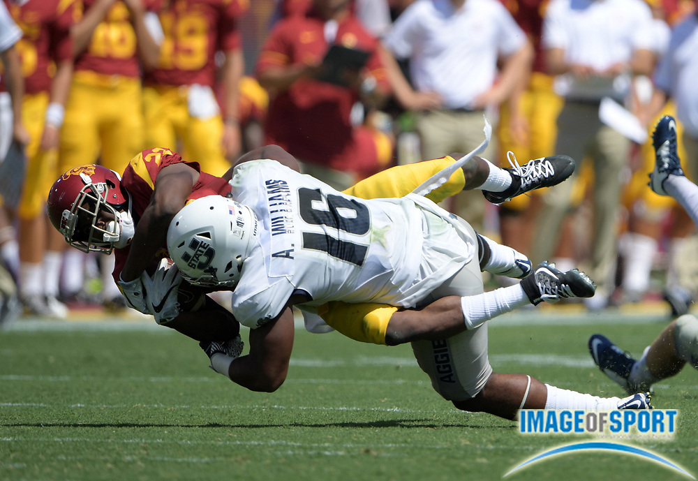 Sep 10, 2016; Los Angeles, CA, USA; USC Trojans running back Justin Davis (22) is tackled by Utah State Aggies cornerback Makiah Gilmer (18) during a NCAA football game at Los Angeles Memorial Coliseum. USC defeated Utah State 45-7.