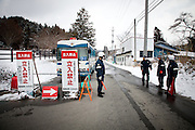 Fukushima  Furumichi  Border of the évacuation zone - Road 288 - March 2012.The road 399 is just over the limit of the Nuclear Evacuation zone and cross the village Furumichi. The nuclear plant is 20 km ahead on the road 288. The policeman stay there with a mask protection. Level of radioactivity : 2.5MicroSV/h